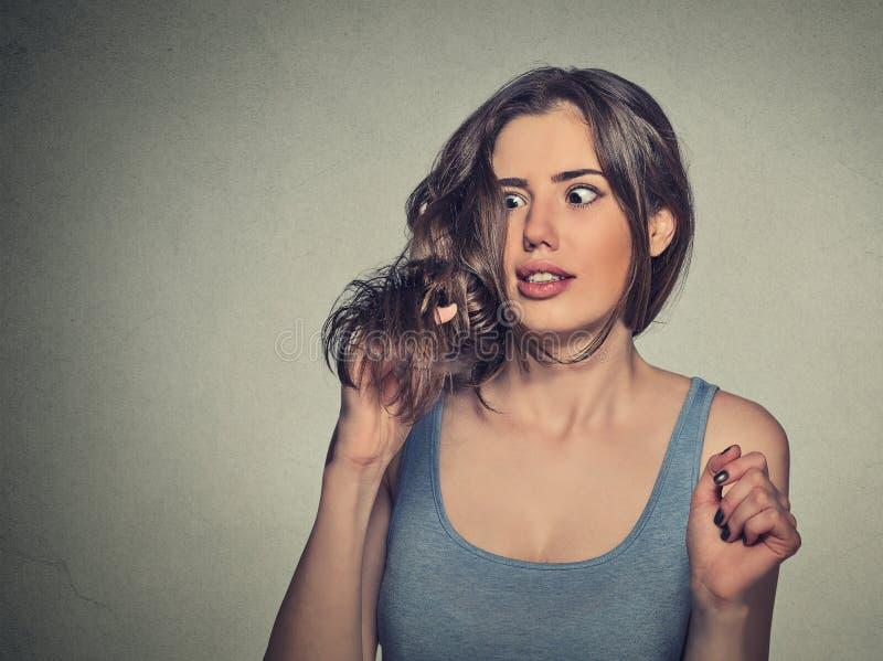 Разочарованная сотрясенная молодая женщина несчастная с ее новым отрезком волос стоковая фотография