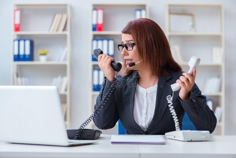 Разочарованный ассистент центра телефонного обслуживания отвечая к звонкам стоковое фото