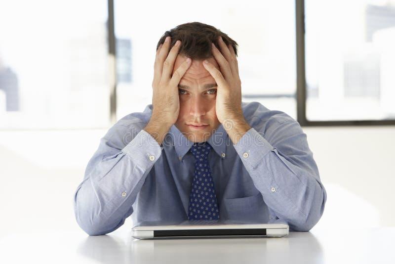 Разочарованный бизнесмен сидя на столе в офисе используя компьтер-книжку стоковое фото rf