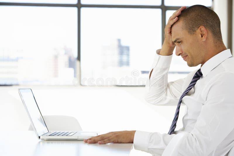 Разочарованный бизнесмен сидя на столе в офисе используя компьтер-книжку стоковые фото