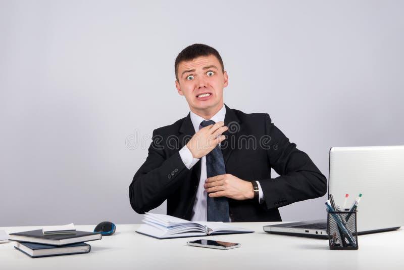 Разочарованный бизнесмен screams и вытягивает на его связи стоковые изображения