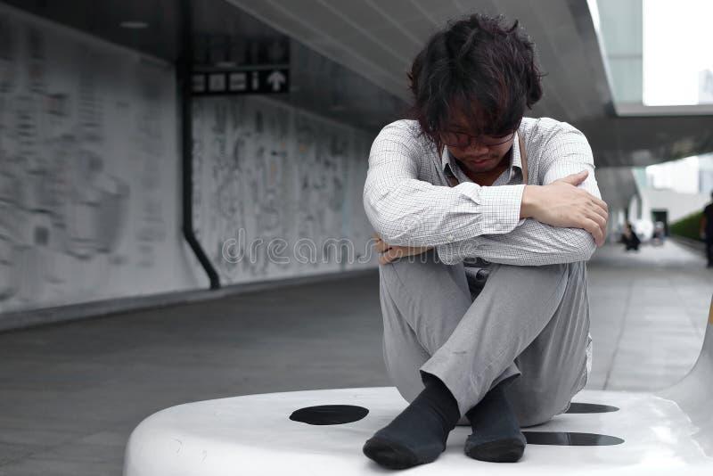 Разочарованный вымотанный молодой азиатский бизнесмен сидит и обнимает его колени до комода стоковые изображения rf