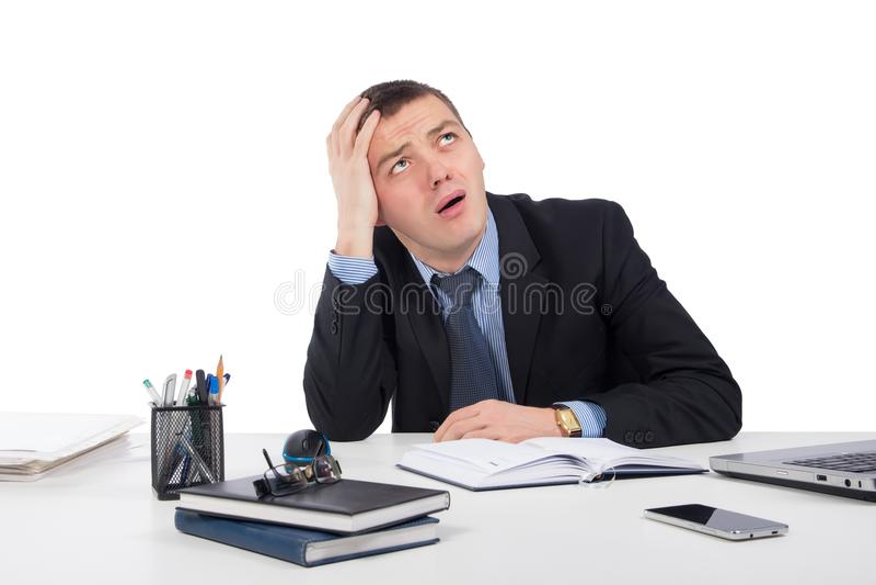 Разочарованный молодой бизнесмен работая на портативном компьютере на офисе стоковая фотография