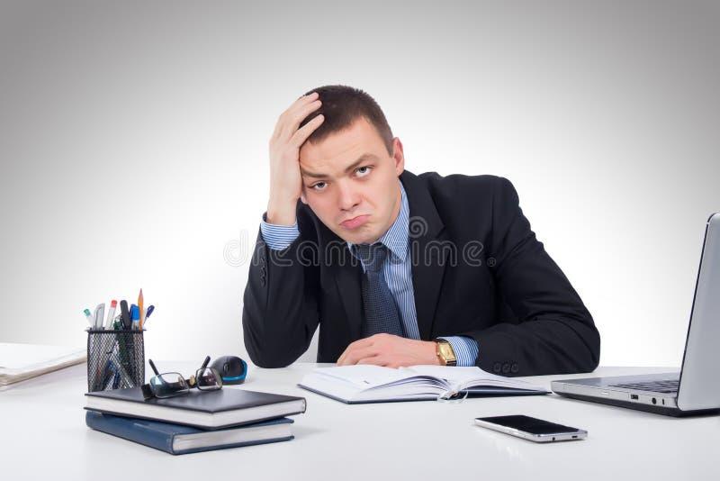 Разочарованный молодой бизнесмен работая на портативном компьютере на offi стоковое изображение rf