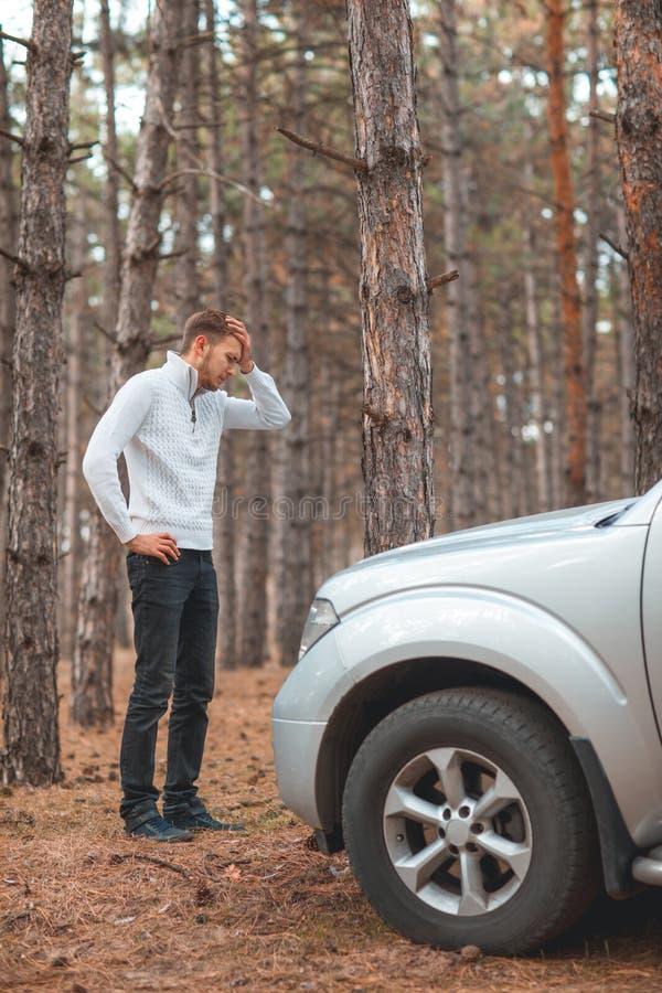 Разочарованный парень, стоящ около сломленного автомобиля и владений его голова стоковое изображение rf
