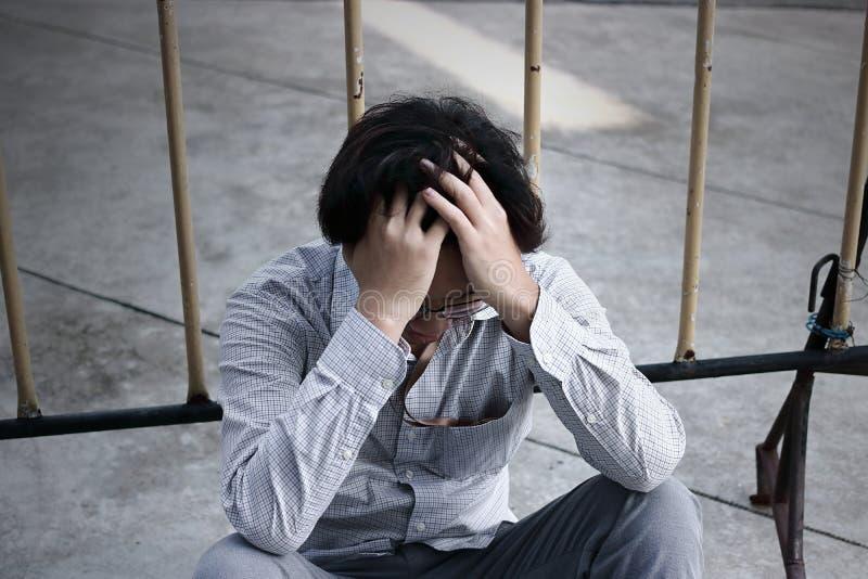 Разочарованный усиленный молодой азиатский лоб заволакивания бизнесмена при руки и чувство разочарованные на внешнем офисе стоковое фото