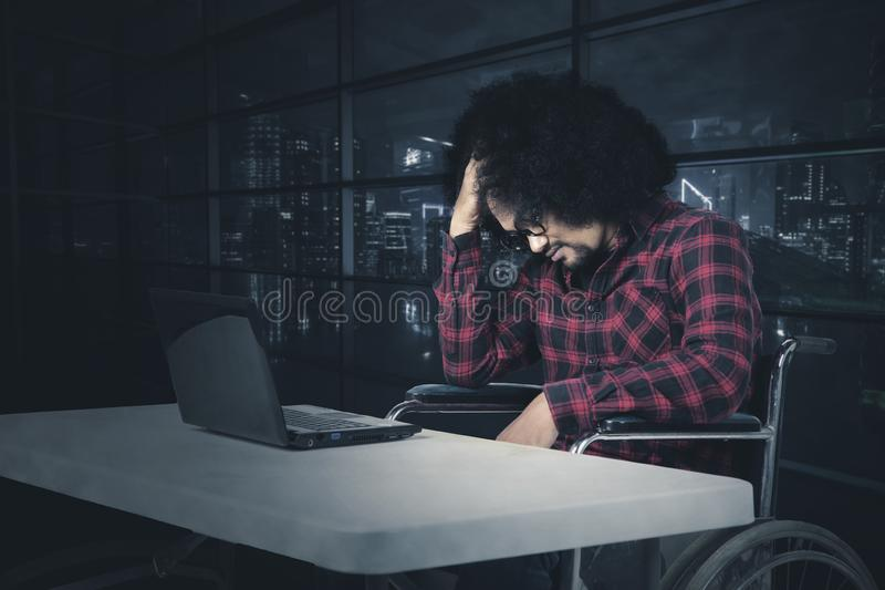 Разочарованный человек работая на кресло-коляске стоковые фотографии rf