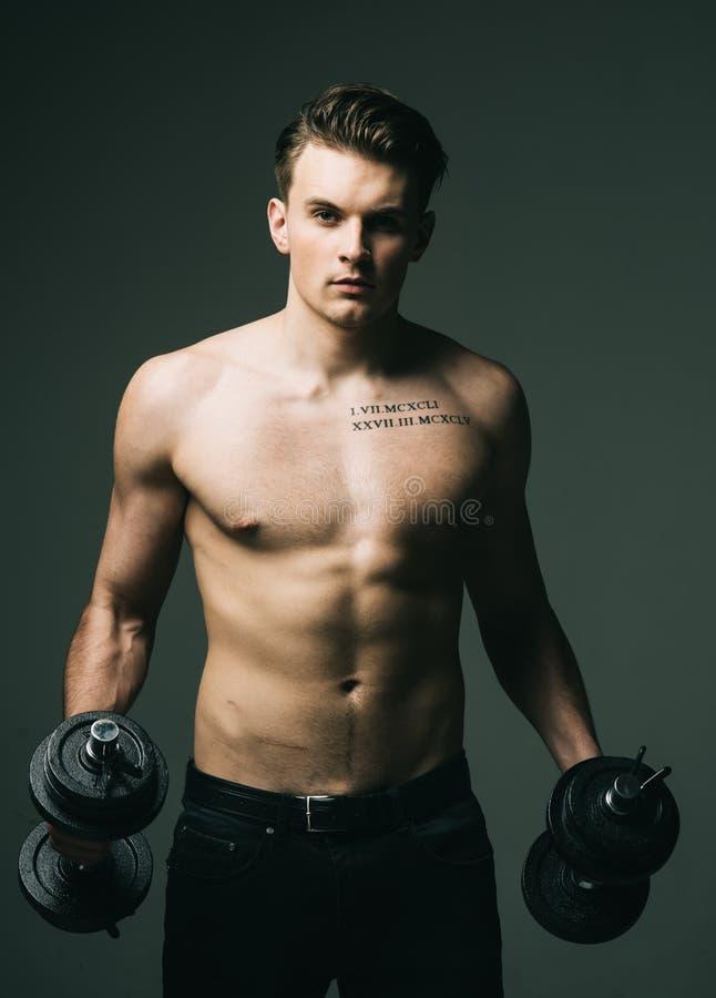 Разработайте концепцию Человек с торсом, мышечное мачо с 6 пакетами, держит гантели, темную предпосылку Гай с татуировкой стоковое фото rf