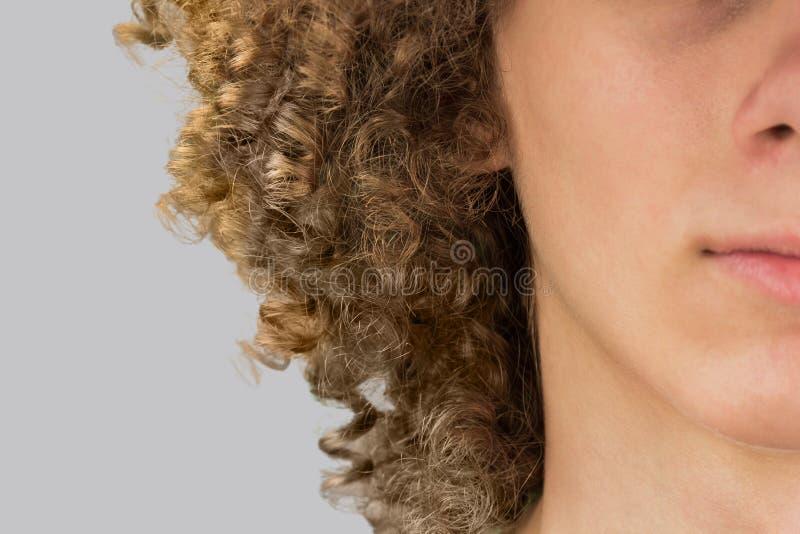 Разрезанный в полуобрезанный портрет молодого кудрявого европейца с длинными вьющимися волосами и закрытыми глазами очень пышные  стоковое изображение