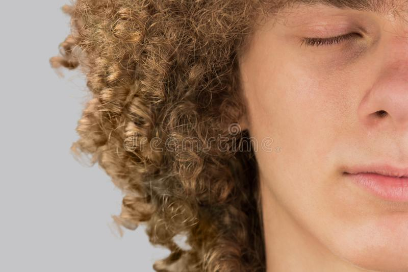 Разрезанный в полуобрезанный портрет молодого кудрявого европейца с длинными вьющимися волосами и закрытыми глазами очень пышные  стоковая фотография rf
