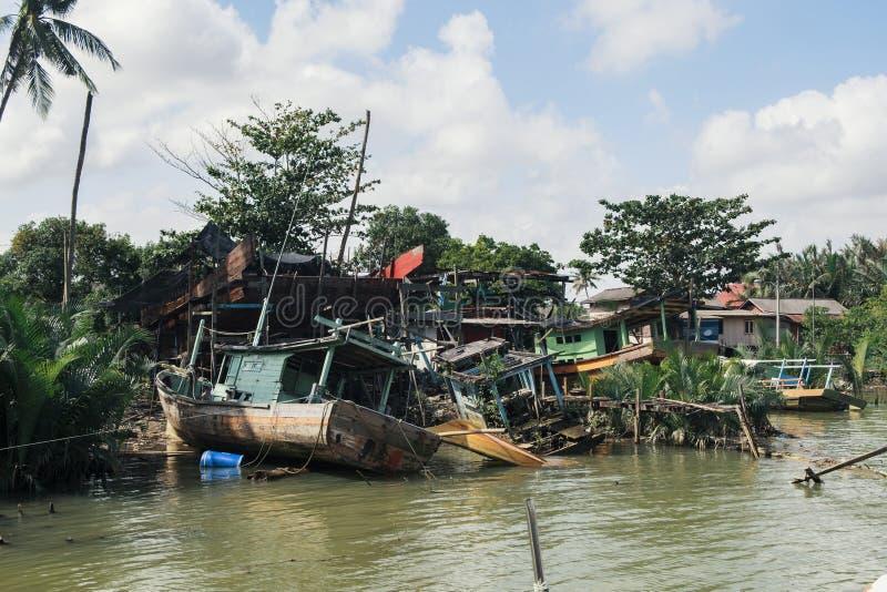 Разрушанная шлюпка рыболова развязности села на мель около берега реки a стоковая фотография rf