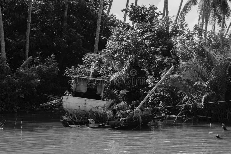 Разрушанная шлюпка рыболова развязности села на мель около берега реки a стоковые фотографии rf