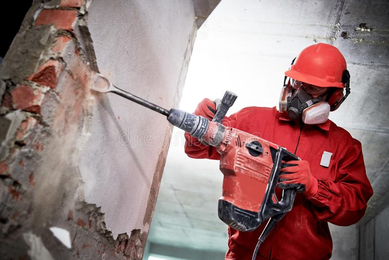 Разрушать подрывания и конструкции работник с молотком ломая штукатурить внутренней стены стоковые фото