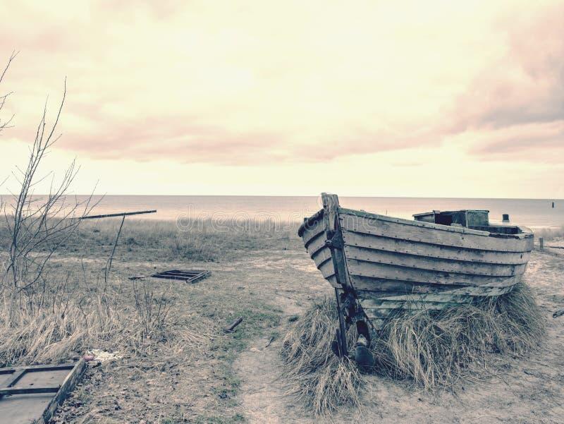 Разрушенная деревянная шлюпка fisher Сломленная покинутая шлюпка в песке залива моря стоковые изображения rf