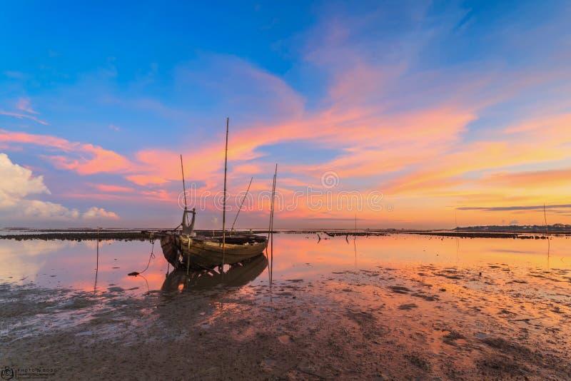 Разрушенная рыбацкая лодка на море с заходом солнца стоковые фотографии rf