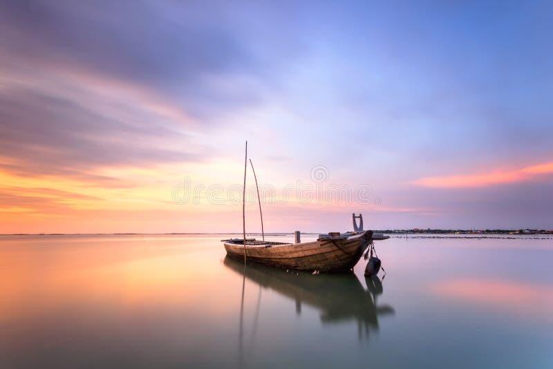 Разрушенная рыбацкая лодка на море с сумерк стоковая фотография rf