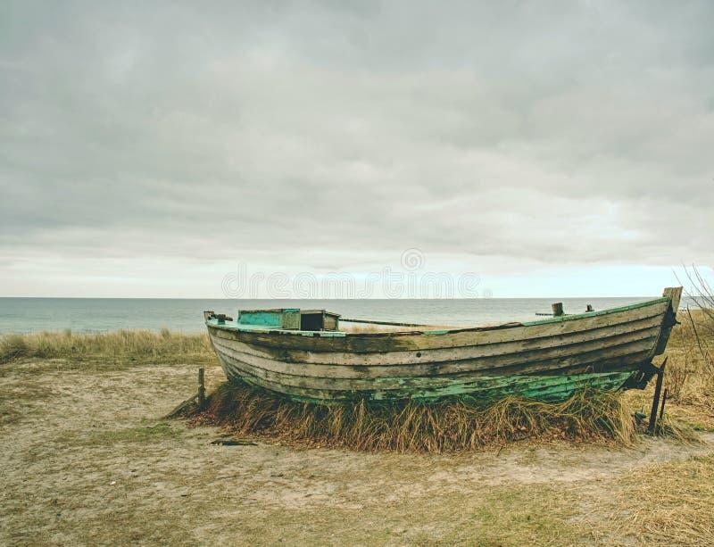 Разрушенная рыбацкая лодка на старой сухой траве Покинутый деревянный корабль с поврежденным двигателем стоковая фотография rf