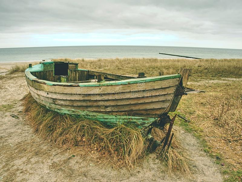 Разрушенная рыбацкая лодка на старой сухой траве Покинутый деревянный корабль с поврежденным двигателем стоковые фото