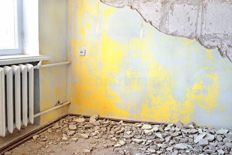 Разрушенный пакостный пустой желтый интерьер с винтажным радиатором стоковая фотография