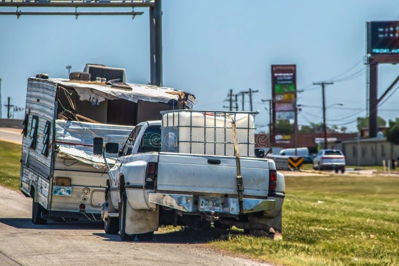 Разрушенный трейлер туриста с частью задней части сорванной около дороги с приемистостью припаркованной перед ей - предпосылка зн стоковая фотография
