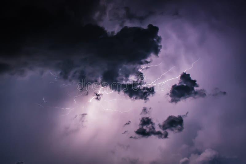 Разрядки удара молнии в фиолетовых облаках шторма на конце ночи стоковая фотография