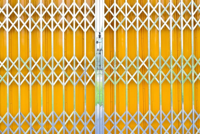 Раздвижная дверь гриля желтого металла с замком пусковой площадки стоковая фотография rf