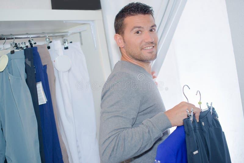 Раздевалка человека входя в с одеждами выбора стоковые изображения rf