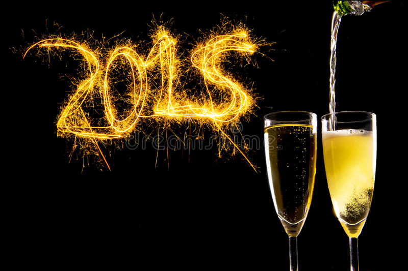 Разлейте заполняя стекла по бутылкам Шампани для праздновать канун 2015 Новых Годов стоковые изображения rf