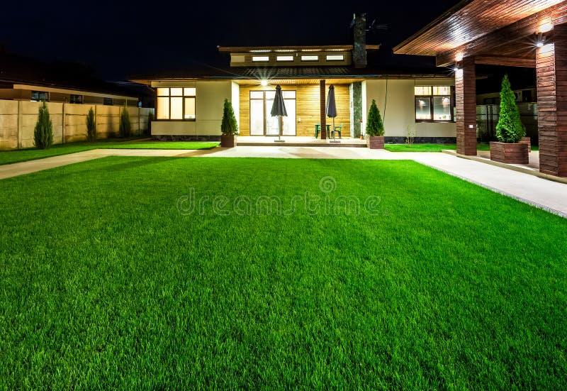 Разделенный дом на взгляде ночи от внешней стороны заднего двора стоковые фотографии rf