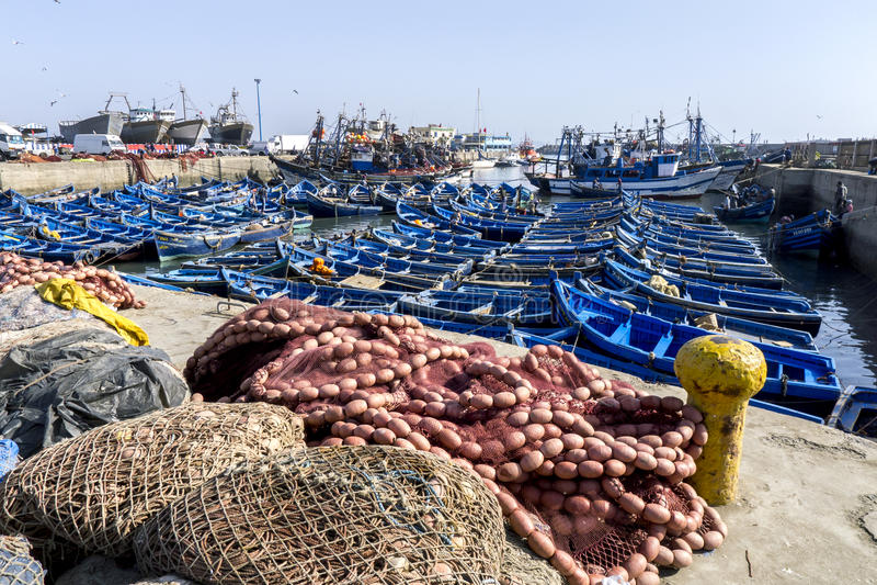 Раздел занятой удя гавани на Essaouira в Марокко показывая рыболовные сети, маленькие лодки и траулеры стоковое фото