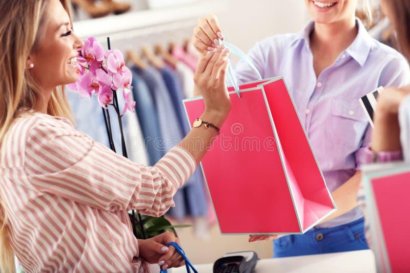 Раздел крупного плана средний женского клиента получая хозяйственные сумки в бутике стоковое фото rf