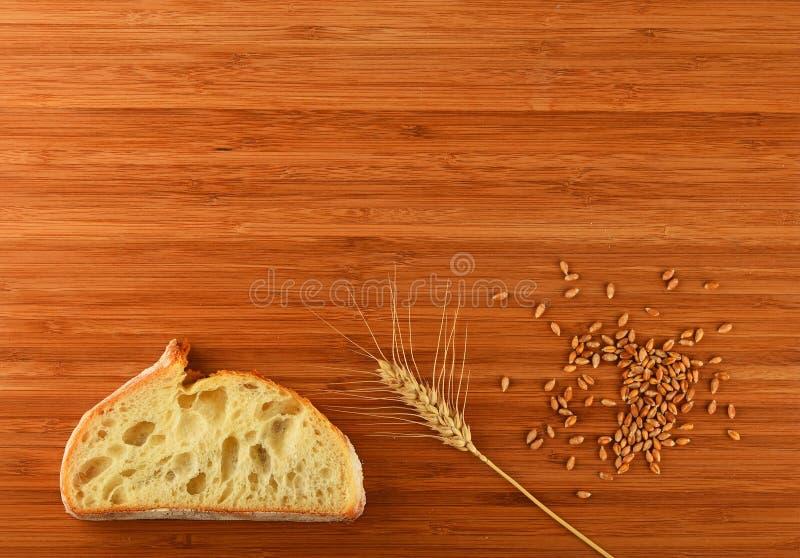 Разделочная доска с ухом, зернами и куском пшеницы хлеба стоковые изображения