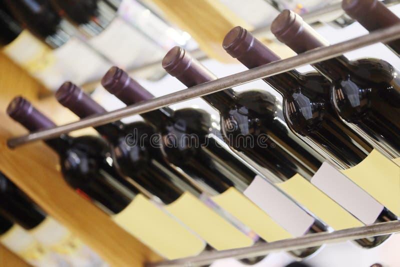 разливает красное вино по бутылкам стоковое изображение