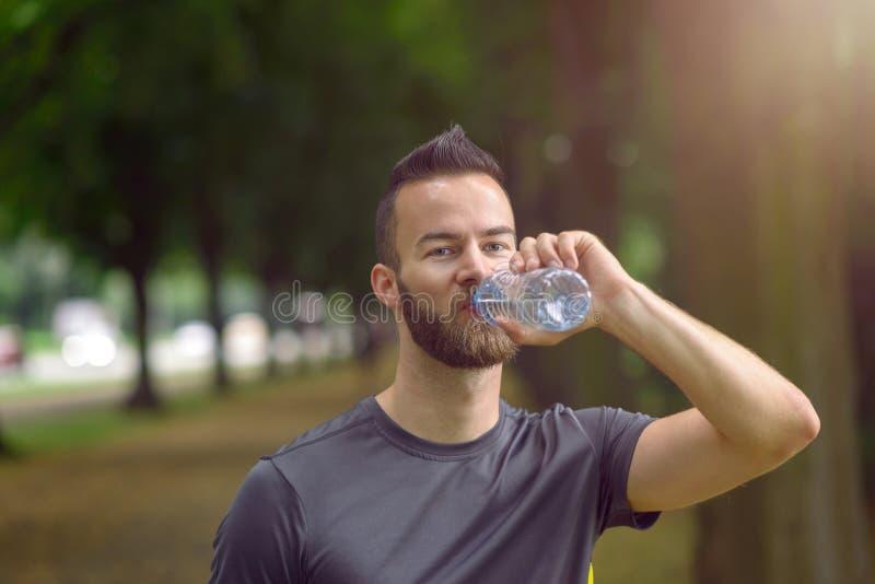 разлитые по бутылкам выпивая детеныши воды человека стоковая фотография