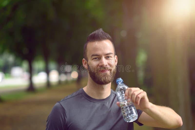 разлитые по бутылкам выпивая детеныши воды человека стоковое изображение rf