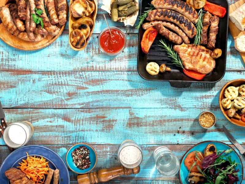 Различная еда сварила на гриле на голубом деревянном столе стоковые фотографии rf