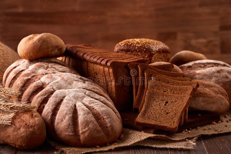 Различные виды хлеба на мешковине на деревянном столе с запачканной коричневой предпосылкой Дизайн плаката кухни или хлебопекарни стоковое изображение rf