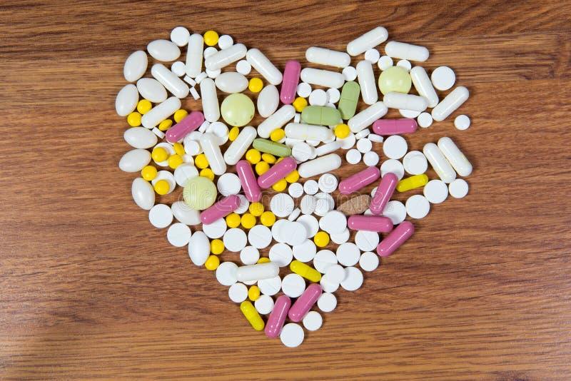 Различные лекарства положены вне на таблицу в форме сердца стоковые фото