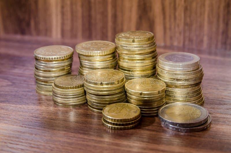 Различные золотые монетки евро на деревянном столе стоковые фотографии rf