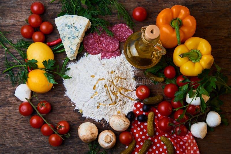 Различные ингридиенты для пиццы Мука, масло, грибы, огурцы, томаты вишни, оливки, моццарелла, сосиска, сыр стоковое изображение