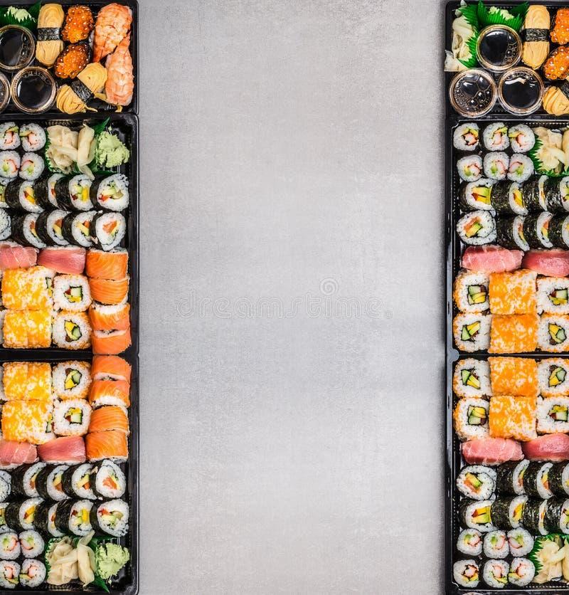 Различные комплекты суш: крены, nigiri, maki и uramaki в черном упаковывая подносе на серой каменной предпосылке, взгляд сверху,  стоковая фотография rf