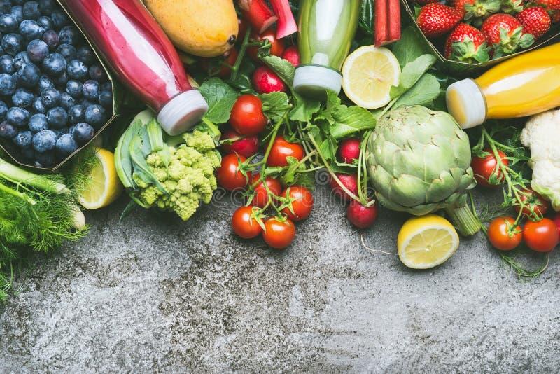 Различные красочные smoothie и соки в бутылках с свежими органическими овощами и плодоовощами на серой конкретной предпосылке, вз стоковые фото