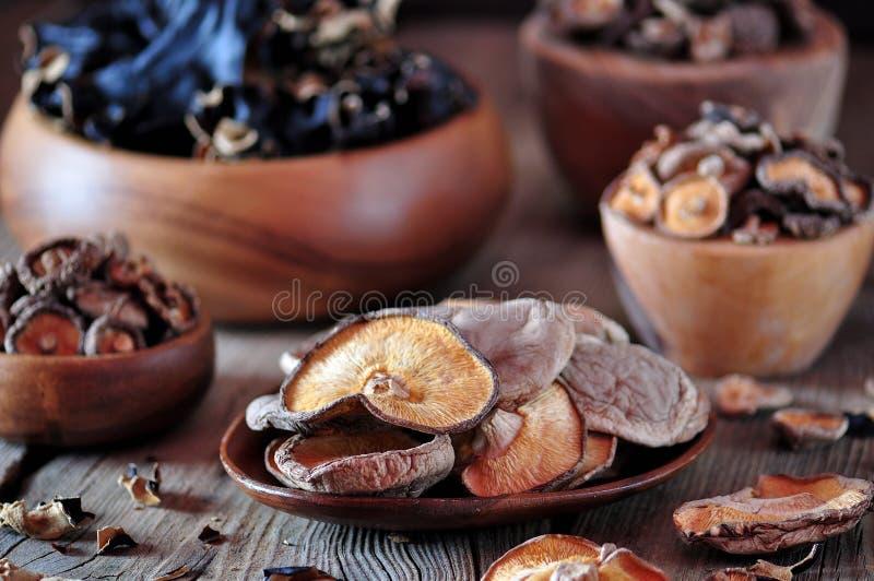 Различные органические высушенные китайские грибы в деревянном шаре на старой деревянной предпосылке стоковые изображения