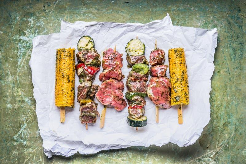 Различные протыкальники мяса для гриля с овощами, ушами мозоли и condiment на зеленой деревенской предпосылке стоковое фото rf