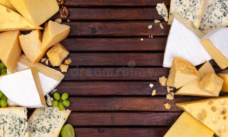 Различные сыры на деревянном столе с пустым космосом Чеддер, пармезан, Эмменталь, голубой сыр Взгляд сверху, космос экземпляра стоковые фотографии rf