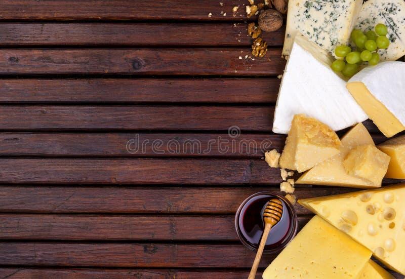 Различные сыры на деревянном столе с пустым космосом стоковые изображения rf
