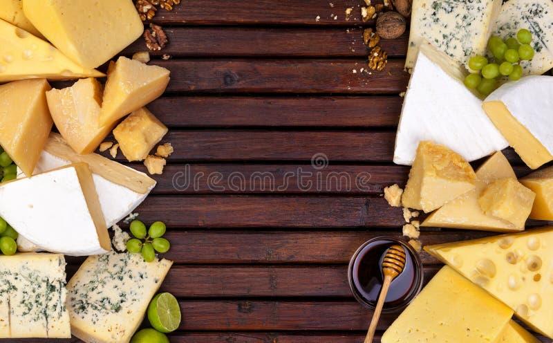 Различные сыры на деревянном столе с пустым космосом стоковые изображения
