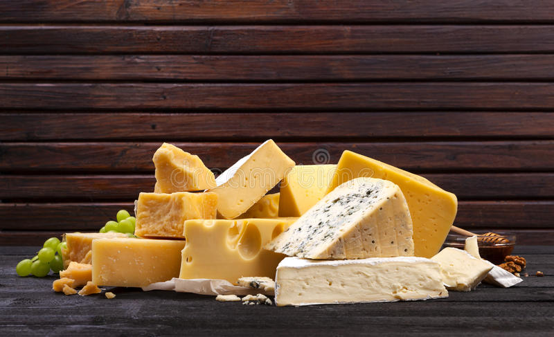 Различные типы сыра на черном деревянном столе стоковая фотография rf