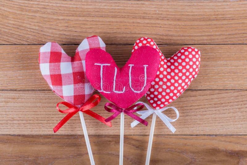 3 различных сердца ткани на деревянных ручках при смычки ленты помещенные на деревянной предпосылке День валентинок фото стоковые фотографии rf