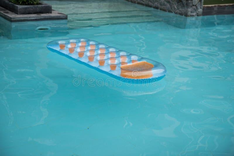 Раздувной голубой и оранжевый тюфяк в бассейне стоковые изображения